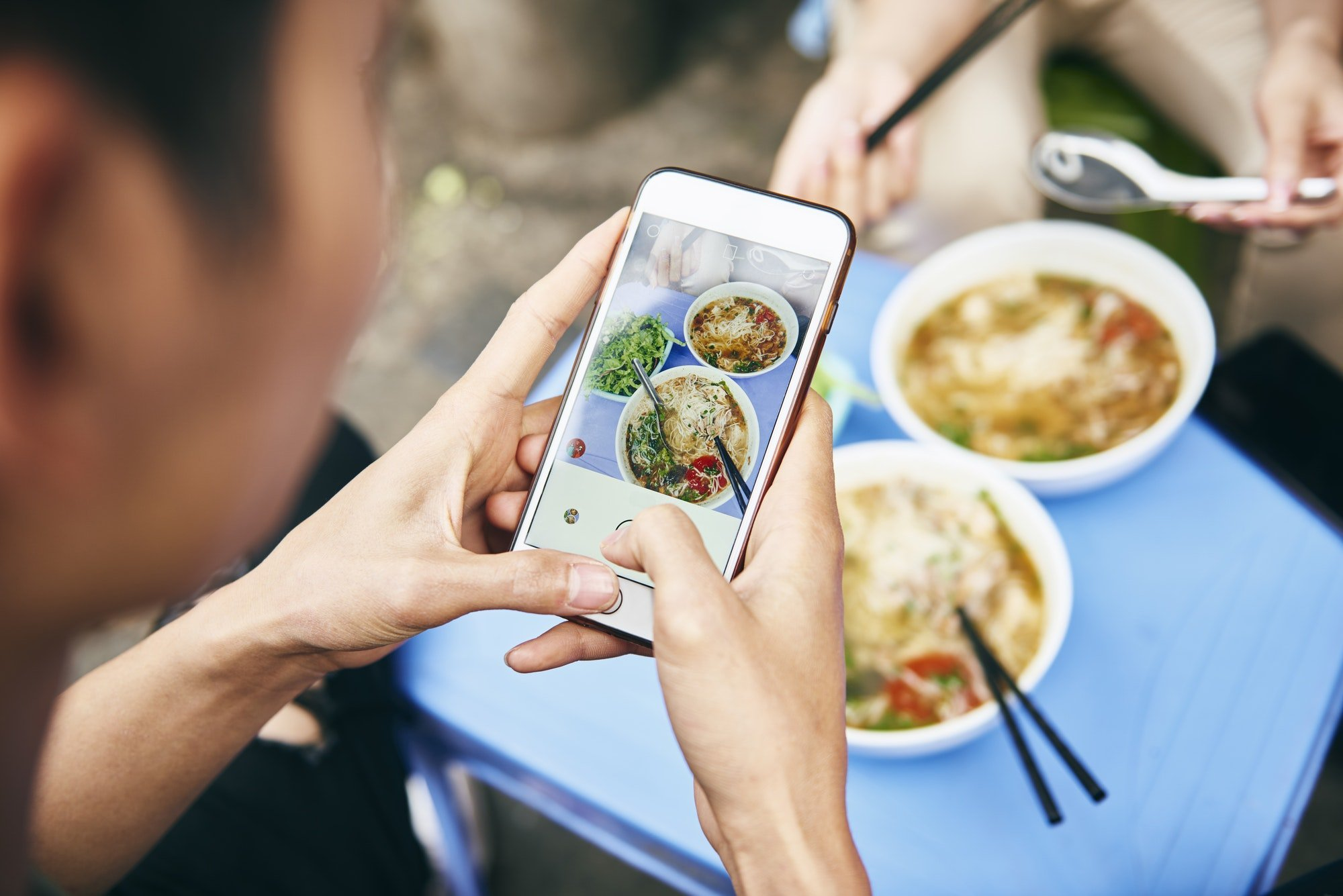 Close up of man photographing his Vietnamese food